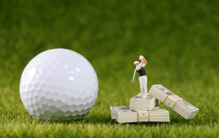 A miniature golfer standing on a wad of hundred dollar bills and a white golf ball.