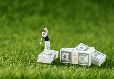A miniature golfer standing on a wad of hundred dollar bills with a lawn background.