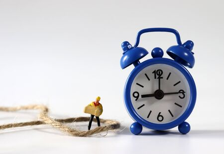 A miniature courier wrapped in a rope next to a blue alarm clock. Stock Photo