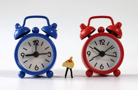 A miniature courier standing between a red and blue alarm clock. Stock Photo