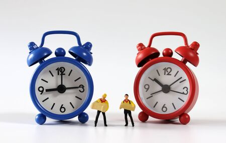 Two miniature couriers standing between a red and blue alarm clock.