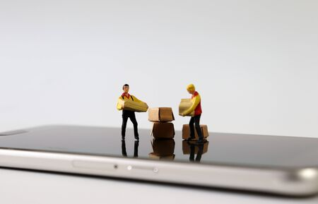 Two miniature couriers standing on top of a Smartphone. Stock Photo