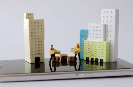 Miniature houses and miniature couriers on top of smartphones. 免版税图像 - 142428140
