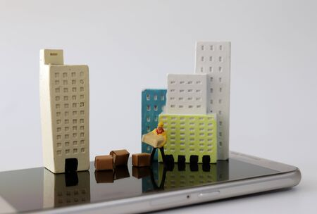 Miniature houses and miniature couriers on top of smartphones.