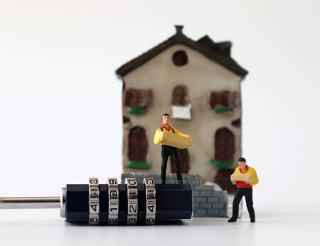 Miniature courier with a lock in front of a miniature house. Stock Photo