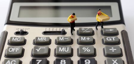 Two miniature couriers standing on a calculator.