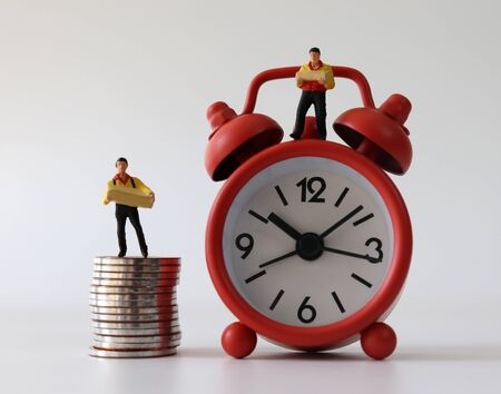 A miniature courier standing on a red alarm clock and a miniature courier standing on a pile of coins.