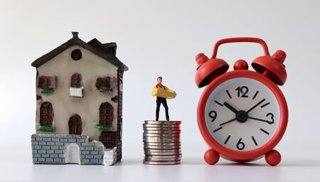 A miniature courier standing on a pile of coins, a miniature house and an alarm clock.