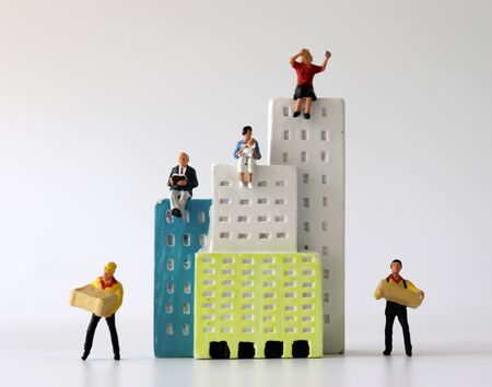 Miniature people sitting on miniature building with miniature couriers.