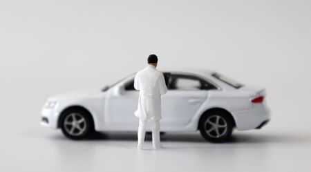 A miniature cars and miniature medical staff on a white background. Stock Photo