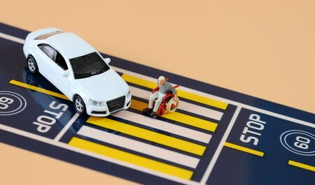 A miniature man in a wheelchair crossing a crosswalk and a miniature car.