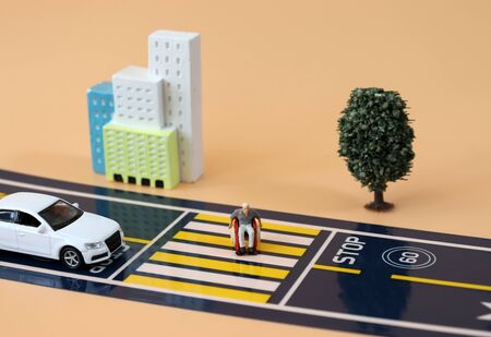 A miniature man in a wheelchair crossing a crosswalk and a miniature car standing on a stop line. Stock Photo