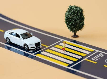 A miniature boy crossing a crosswalk and a miniature car standing on a stop line. Stock Photo