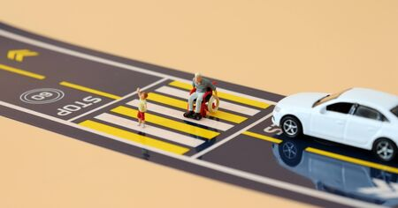 A miniature child with a hand raised and a miniature man in a wheelchair crossing a crosswalk.