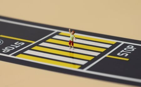 A miniature boy who raises his hand and crosses the crosswalk.