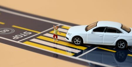 A miniature boy who raises his hand and crosses the crosswalk a miniature car that crossed the stop line. Stock Photo