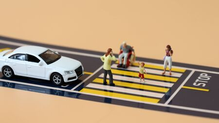 Miniature cars standing at a stop line and miniature people crossing crosswalks.