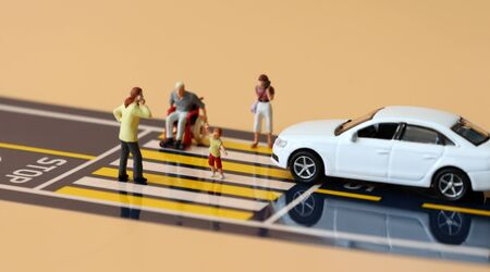 Miniature cars that crossed the stop line and miniature people crossing crosswalks.