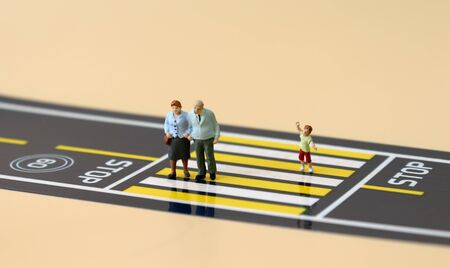 A miniature old couple and a miniature boy crossing a crosswalk. Stock Photo