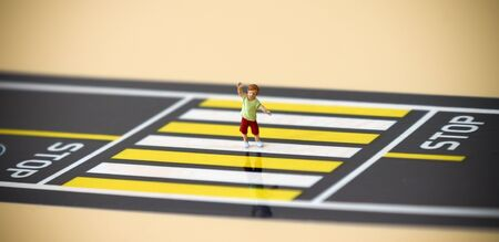 A miniature child with a hand raised crossing a crosswalk. Stock Photo