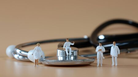 Stethoscope and Miniature medical staff.