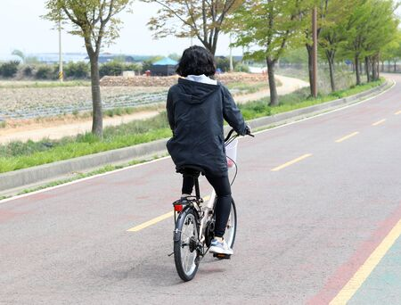 The back of a woman riding a bicycle.