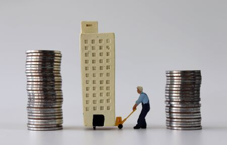 A miniature man who moves a miniature building from a pile of high coins to a pile of low coins.