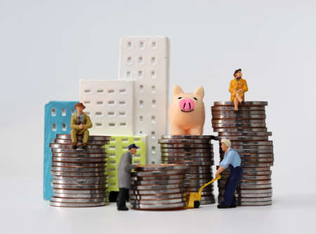 Miniature people carrying a pile of coins. Miniature house and miniature people on a pile of coins. 版權商用圖片