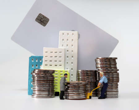 Miniature people carrying a pile of coins. Pile of coins and credit card. 版權商用圖片