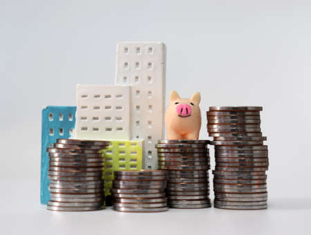 Miniature house and a miniature piggy bank on a pile of coins.