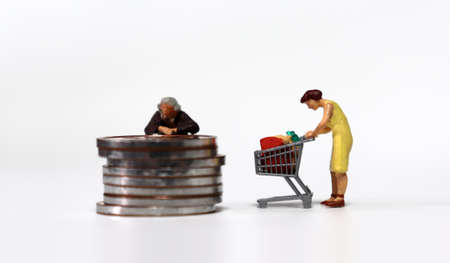 A miniature woman with a pile of coins and a miniature woman with a shopping cart.
