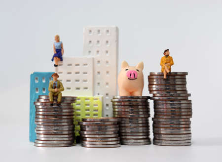 Miniature house and miniature people on a pile of coins.