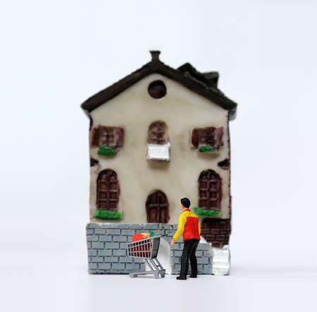 Miniature delivery driver with shopping cart in front of miniature house.