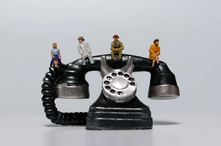 Miniature people sitting on miniature phones. Concepts that recommend non-face-to-face meetings.
