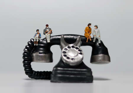Miniature people wearing masks and sitting on miniature phones. Concepts that encourage social distance and non-face-to-face contact.