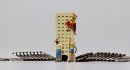 Miniature people trying to climb a miniature building with coins. The concept of deepening job shortages.