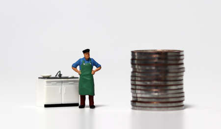 A pile of coins and a miniature people. The concept of disaster support for self-employed people.