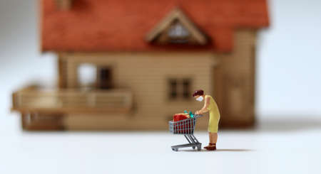 Miniature people wearing masks. Concepts about recommending wearing a mask when going out to purchase daily necessities.