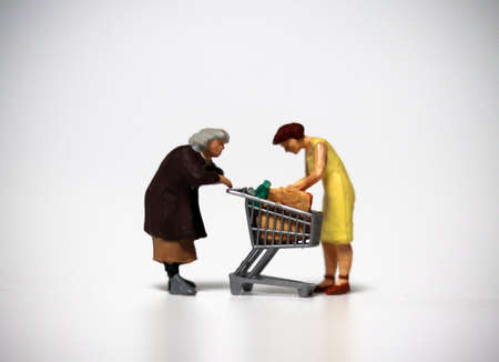 One shopping cart and two miniature women. The concept of shortage of daily necessities.