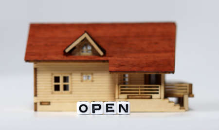 Close-up on a'OPEN' and a miniature house. Concepts about restaurants that are starting to reopen.