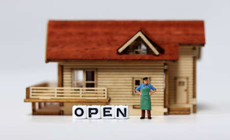 Close-up on a'OPEN' and a miniature man. Concepts about shops that are starting to reopen.