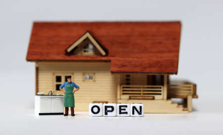 Close-up on a'OPEN' and a miniature man. Concepts about restaurants that are starting to reopen. 免版税图像