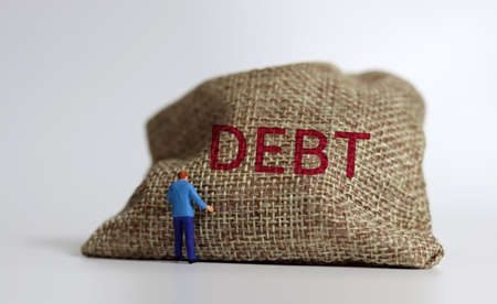 A bundle bearing the word DEBT and a miniature man standing. A warning concept about the risk of increasing debt.