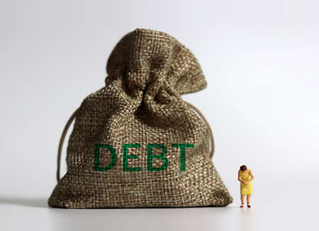 A bundle bearing the word DEBT a bundle and a miniature woman standing with her head down. The concept of the risk of excessive debt.