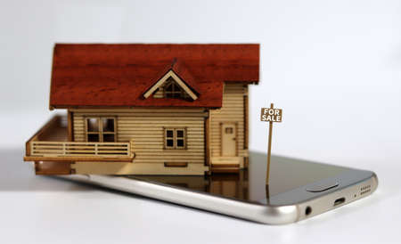 """Miniature house with a sign written """"For Sale"""" on the smartphone. The concept of non-face-to-face real estate brokerage."""