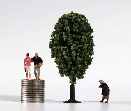 Piles of coins and miniature tree and miniature people