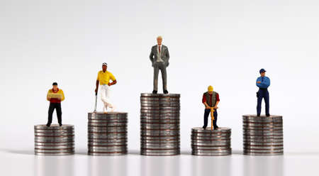 Various miniature people standing on piles of coins of different heights. The concept of economic inequality.