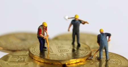 Miniature people holding tools on Bitcoin. Miniature and business concept.