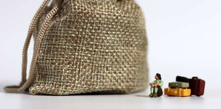 bundle and a miniature woman standing with her head down. The concept of the risk of excessive debt.
