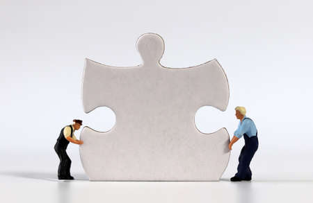 Two miniature men carrying puzzle piece. Puzzle pieces and miniature people.